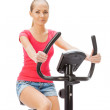 Young womuses stationary bicycle trainer. — Stock Photo #40525531