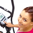 Young woman uses elliptical cross trainer. — Stock Photo #41476605
