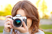 Young woman uses digital slr photocamera. — Stock Photo