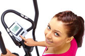 Young woman uses elliptical cross trainer. — Stock Photo