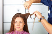 Hair salon. Woman haircut. Use of straightener. — Stock Photo