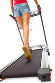 Young woman uses treadmill. — Stock Photo