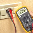 Metering socket voltage with digital multimeter — Stock Photo #32331593