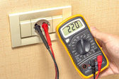 Metering socket voltage with digital multimeter — Stock Photo