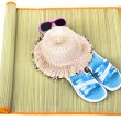 Beach accessories on straw mat over white — Stock Photo #47409241