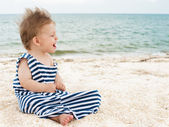Cute little boy on the beach in a striped t-shirt — Stock Photo