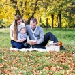 Happy family in autumn park reading a book — Stock Photo