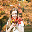 Cute young girl in autumn park with flowers — Stock Photo