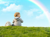 Cute little boy sitting on the green grass with a toy bunny — Stock Photo