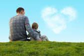 Little boy with his father sitting on the green grass — Stock Photo