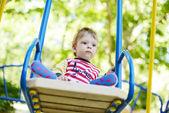 Cute little boy riding on a swing — Stock Photo