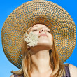 Girl in a hat on a background of blue sky — Stock Photo