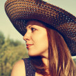 Beautiful young woman in a hat outdoors. — Stock Photo
