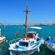 Traditional Greek boat in white and blue colors bobs on the waves on a clear sunny day. — Stock Photo