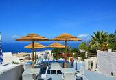 Arka plan üzerinde deniz ve palmiye ağaçları, santorini, yunanistan adada şemsiyelerle café. — Stok fotoğraf