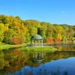 Gazebo and a bridge on a lake in autumn park — ストック写真