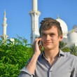 Smiling young man with a cell phone in front of mosque — Stock Photo