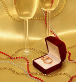 Wedding rings and stemware with sparkling wine on a golden background — Stock Photo