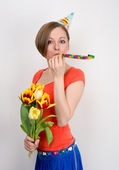 Woman celebrating birthday with tulips and party hat — Stock Photo