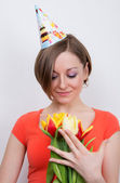 Woman celebrating birthday with tulips, party hat — Stock Photo