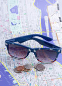 Sunglasses and U.S. coins on the map. — Stock Photo