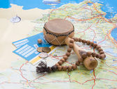 Drum, rosary, tickets and Arabian coins on the map. — Foto de Stock