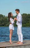 Homem e mulher de mãos dadas em um cais de madeira perto da água. — Fotografia Stock