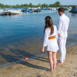 Man and woman standing on the river bank and see off toy boat wi — Stockfoto #48626493
