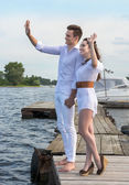 Guy holds the girl's hand on a wooden pier near the water. — Fotografia Stock