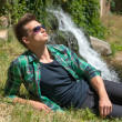 Guy in sunglasses relaxing in nature near the waterfall — Stock Photo #48760091