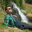 Guy in sunglasses relaxing in nature near the waterfall — Stock Photo #48760107