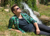 Guy in sunglasses relaxing in nature near the waterfall — Stock Photo