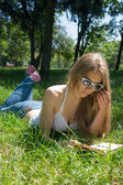 Girl in sunglasses reading a book in a summer park — Stock Photo