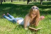 Dziewczyna trzyma czerwony jabłko i czytając książkę w lato — Zdjęcie stockowe