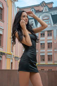 Beautiful girl talking on a mobile phone on a city street. — Stock Photo