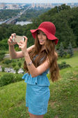 Beautiful woman in a red hat taken picture of herself, selfie. — Stock Photo
