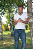 Young man in the park with cell phone — Stock Photo