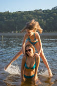Girl jumping in the water. Girl and mom playing water games on t — Stock Photo