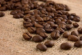 Kávová zrna na pytlovina zblízka — Stock fotografie