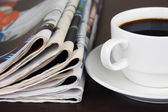 Pile of newspapers and cup of coffee on the table — Stock Photo