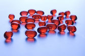 Red vitamin pills in blue light — Stock Photo