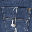 Earphones hanging out of jeans pocket. Music in your pocket — Stock Photo