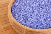 Sea salt enriched with lavender oil in wooden bowl close up — Stockfoto