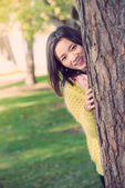 Woman hiding behind a tree — 图库照片