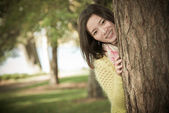 Woman hiding behind a tree — Stock Photo