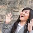 Woman laughing by a stone wall — Stock Photo