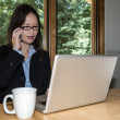 Woman with laptop and coffee on phone — Stock Photo