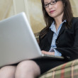 Woman on sofa on laptop — Stock Photo