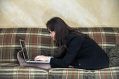 Woman typing on laptop on sofa — Stock fotografie