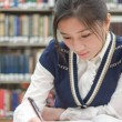 Student doing homework near bookshelf — Stock Photo